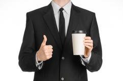 Thème de café de déjeuners d'affaires : homme d'affaires dans un costume noir tenant une tasse de papier blanc de café blanche av Image libre de droits
