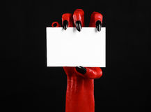 Thème de Halloween : Main de diable rouge avec les clous noirs tenant une carte blanche vierge sur un fond noir Image libre de droits