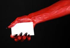 Thème de Halloween : Main de diable rouge avec les clous noirs tenant une carte blanche vierge sur un fond noir Image stock