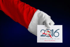 Thème 2016 de Noël et de nouvelle année : Main de Santa Claus jugeant une carte cadeaux blanche sur un fond bleu-foncé dans le st Image libre de droits