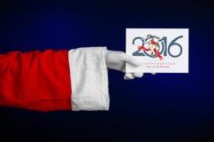 Thème 2016 de Noël et de nouvelle année : Main de Santa Claus jugeant une carte cadeaux blanche sur un fond bleu-foncé dans le st Photographie stock libre de droits
