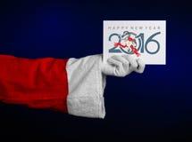 Thème 2016 de Noël et de nouvelle année : Main de Santa Claus jugeant une carte cadeaux blanche sur un fond bleu-foncé dans le st Images stock