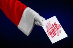 Thème 2016 de Noël et de nouvelle année : Main de Santa Claus jugeant une carte cadeaux blanche sur un fond bleu-foncé dans le st Photos stock