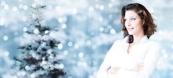 Thème de Noël, femme de sourire d'affaires sur les lumières lumineuses brouillées Photographie stock libre de droits