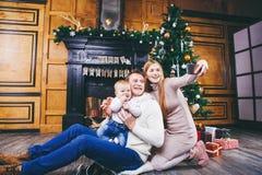 Thème de Noël la jeune famille avec le garçon blond d'un an s'assied sur le plancher en bois sur le fond d'un arbre de Noël avec  Photos stock