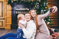 Thème de Noël la jeune famille avec le garçon blond d'un an s'assied sur le plancher en bois sur le fond d'un arbre de Noël avec  Images libres de droits