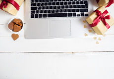 Thème de Noël Ordinateur, cadeaux et biscuits sur la table en bois Photos stock