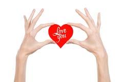 Thème de Saint-Valentin et d'amour : la main tient une carte de voeux sous forme de coeur rouge avec les mots vous aiment a isolé photographie stock libre de droits
