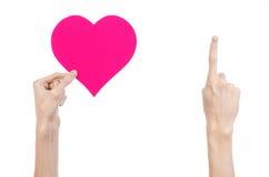 Thème de Saint-Valentin et d'amour : remettez juger un coeur rose d'isolement sur un fond blanc Image libre de droits