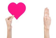 Thème de Saint-Valentin et d'amour : remettez juger un coeur rose d'isolement sur un fond blanc Photo stock