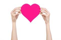 Thème de Saint-Valentin et d'amour : remettez juger un coeur rose d'isolement sur un fond blanc Photo libre de droits