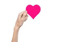 Thème de Saint-Valentin et d'amour : remettez juger un coeur rose d'isolement sur un fond blanc Photographie stock