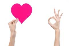Thème de Saint-Valentin et d'amour : remettez juger un coeur rose d'isolement sur un fond blanc Images libres de droits
