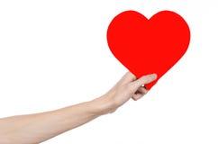 Thème de Saint-Valentin et d'amour : remettez juger un coeur rouge d'isolement sur un fond blanc Image libre de droits