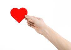 Thème de Saint-Valentin et d'amour : remettez juger un coeur rouge d'isolement sur un fond blanc Photo stock