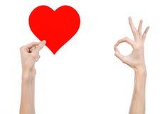 Thème de Saint-Valentin et d'amour : remettez juger un coeur rouge d'isolement sur un fond blanc Images libres de droits