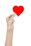 Thème de Saint-Valentin et d'amour : remettez juger un coeur rouge d'isolement sur un fond blanc Photographie stock