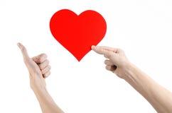 Thème de Saint-Valentin et d'amour : remettez juger un coeur rouge d'isolement sur un fond blanc dans le studio Image stock