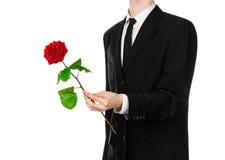 Thème de Saint-Valentin et de jour des femmes : la main de l'homme dans un costume jugeant une rose rouge d'isolement sur le fond Images libres de droits