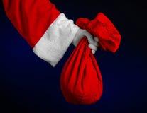 Thème de Santa Claus : Santa tenant un grand sac rouge avec des cadeaux sur un fond bleu-foncé Photos stock