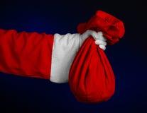 Thème de Santa Claus : Santa tenant un grand sac rouge avec des cadeaux sur un fond bleu-foncé Photo stock