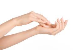 Thème de soin de santé et de corps : belle main femelle avec de la crème blanche d'isolement sur un fond blanc, massage de main Photo stock