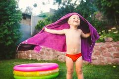 Thème de vacances d'été Un garçon petits 3 caucasien an jouant dans l'arrière-cour d'une maison sur l'herbe près d'une Co gonflab image stock