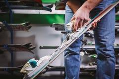 Thème de vente d'affaires et service d'équipement de ski Les mains du jeune homme caucasien ont des skis de montagne, vérifient e image libre de droits