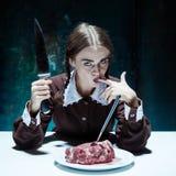 Thème ensanglanté de Halloween : fille folle avec un couteau, une fourchette et une viande Images libres de droits