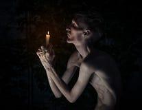 Thème gothique et de Halloween : un homme avec une bougie sur ses genoux avec ses yeux fermés et priants, cire chaude sur ses mai Image libre de droits