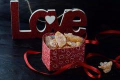 Thème romantique La boîte avec les tranches oranges glacées, amour se connectent le fond abstrait noir Jour du ` s de St Valentin Image libre de droits