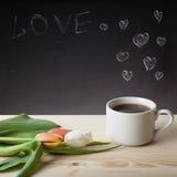 Thème romantique sur un tableau derrière une table en bois avec la tasse de Image stock