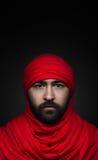 Thème turc et arabe : bel homme musulman avec une barbe dans un foulard rouge d'isolement sur un fond noir dans le studio photos libres de droits