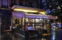 Théâtres parisiens typiques de Deux de café au prochain hôtel de ville localisé par nuit pluvieuse de Paris photos stock