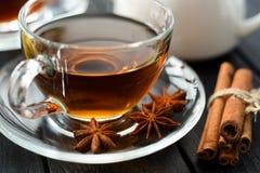 Thé épicé chaud avec l'anis de cannelle et d'étoile dans la tasse en verre sur le blac Image stock