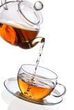 Thé étant renversé dans la cuvette de thé en verre Photos stock