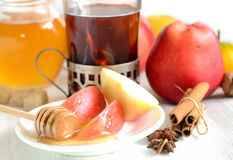 Thé aromatisé dans un anis en verre, de cannelle, de pommes, de miel et d'étoile sur un fond clair Photographie stock libre de droits