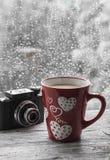 Thé au lait dans la tasse rouge et vieil appareil-photo sur une surface en bois lumineuse Image libre de droits