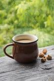 Thé au lait et des biscuits sur une surface en bois légère contre la fenêtre Image libre de droits