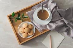 Thé avec des biscuits dans l'assiette creuse blanche avec le papier et le crayon photos libres de droits