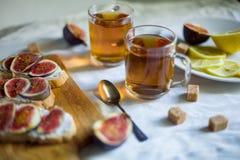 Thé avec des snaks avec les figues et le fromage fondu Photo stock