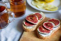 Thé avec des snaks avec les figues et le fromage fondu sur le fond blanc de textile Photographie stock libre de droits