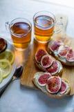 Thé avec des snaks avec les figues et le fromage fondu sur le fond blanc de textile Images stock
