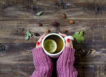 Thé avec le citron dans des ses mains Vue supérieure Photographie stock libre de droits