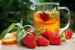 Thé avec le citron et les fraises dans le jardin sur une table en bois Photos libres de droits