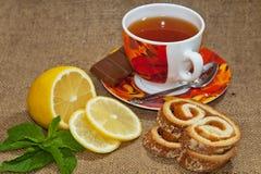 Thé avec le citron, menthe sur un fond de jute Photographie stock