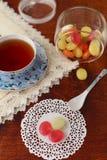 Thé avec les sucreries de sucre colorées Photographie stock libre de droits