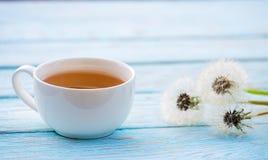 Thé chaud avec un bouquet des pissenlits Photos libres de droits