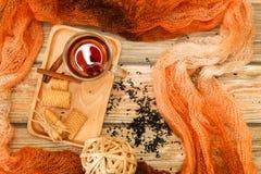 Thé chaud dans la tasse en verre avec des feuilles de thé et des biscuits de bâtons de cannelle sur la table en bois et l'écharpe photographie stock