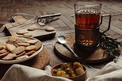 Thé chaud dans le support de tasse antique avec des biscuits de sucre sur le vieux fond en bois brun Type rustique photo libre de droits